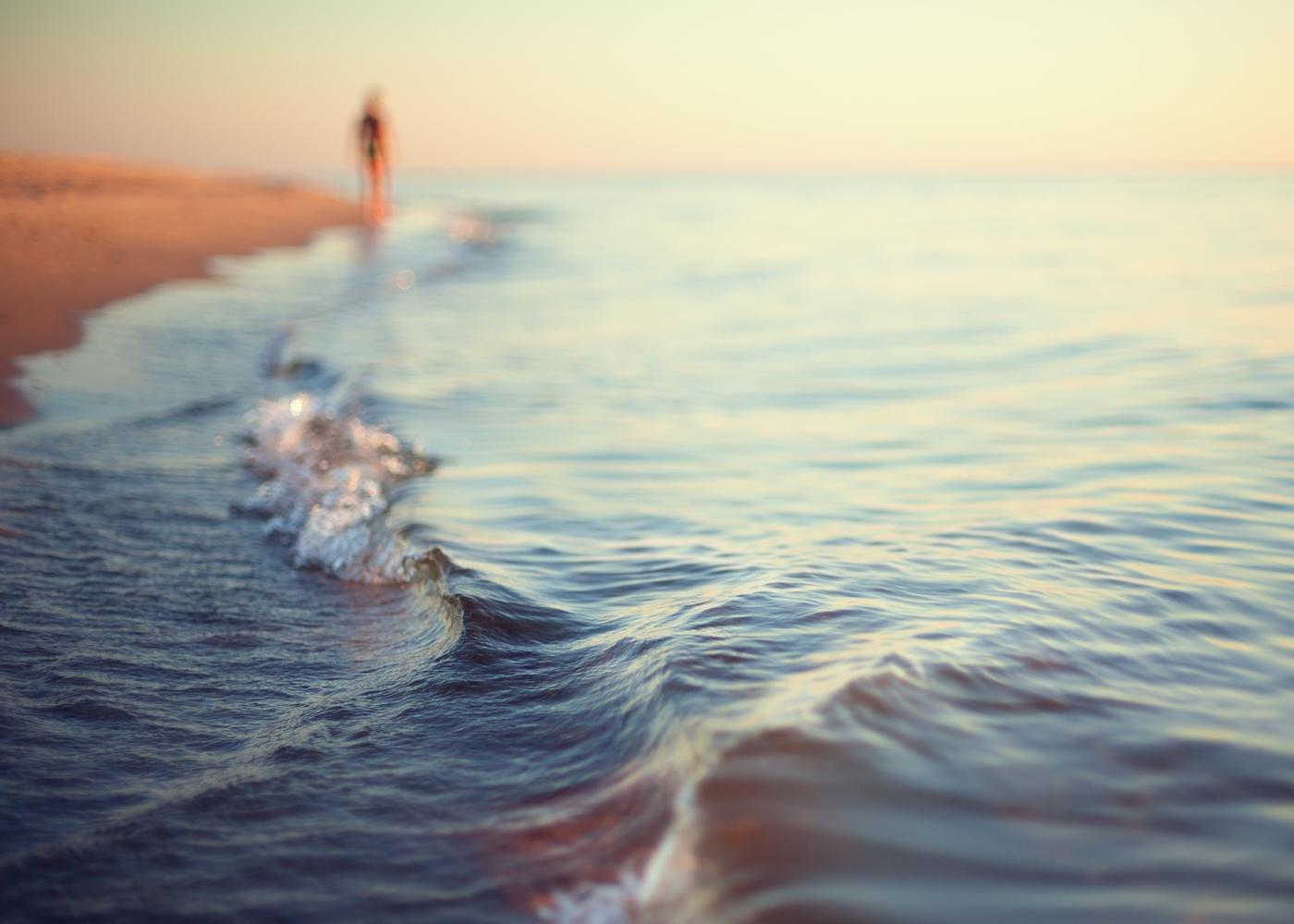 Mulher a caminhar à beira-mar num fim de tarde