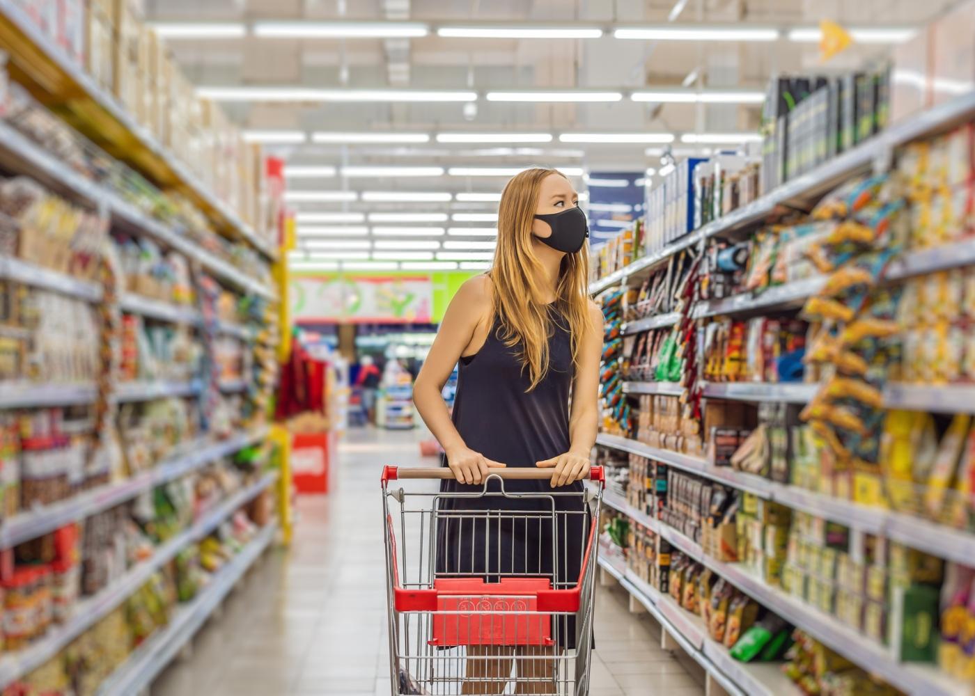 Mulher no supermercado com máscara de tecido