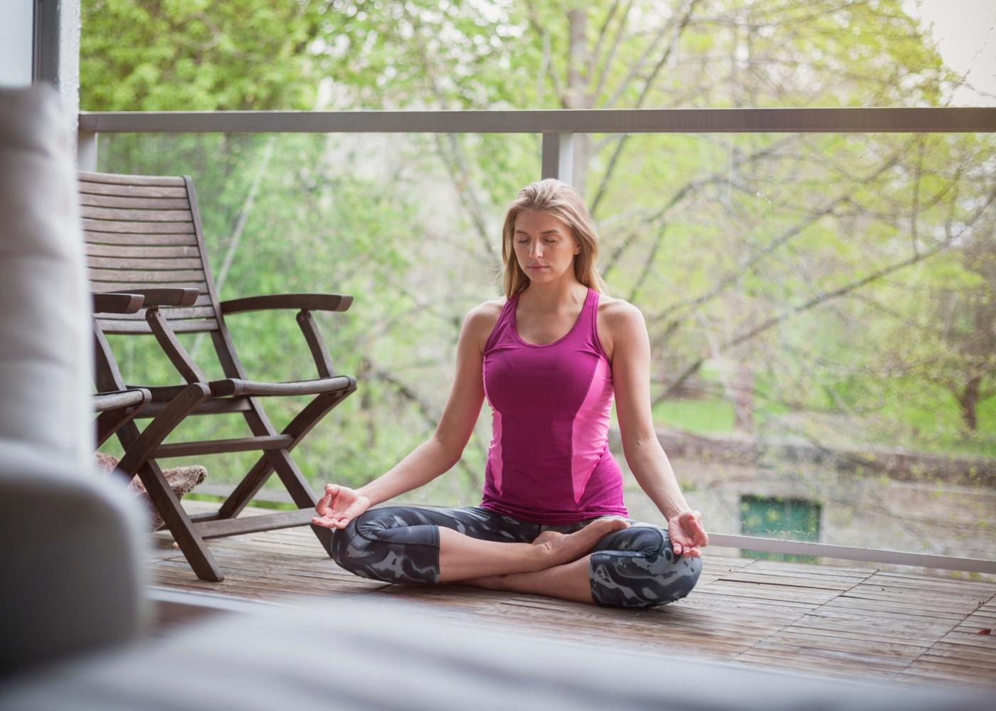 Mulher a meditar na varanda de casa