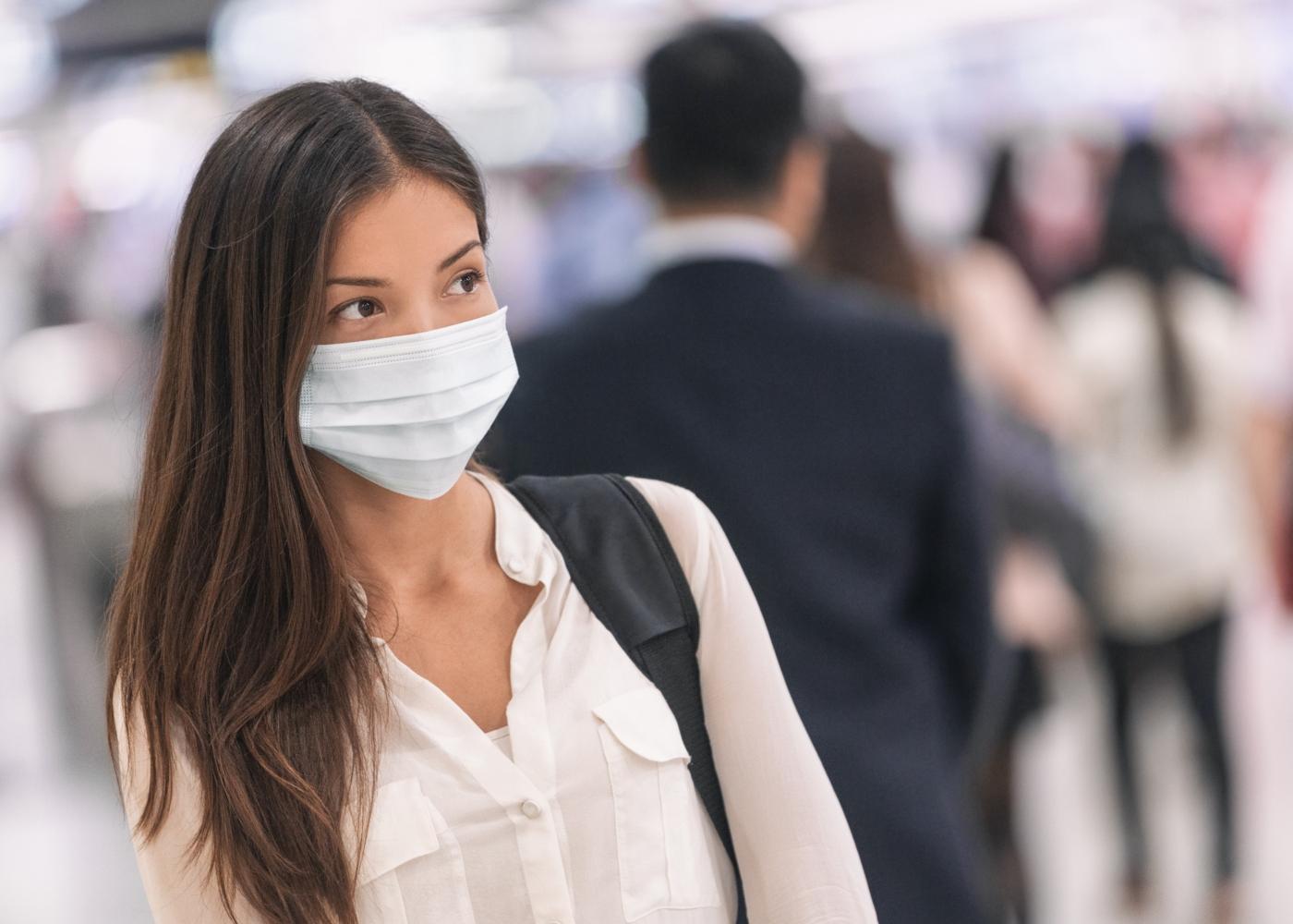 Mulher no metro com máscara