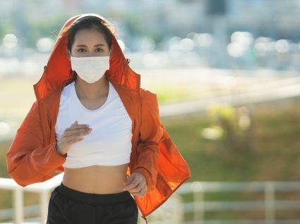 Usar máscara para praticar desporto: mulher a correr ao ar livre com máscara de proteção
