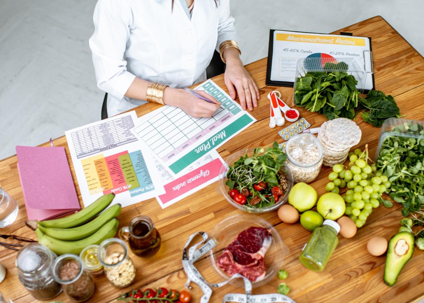 Nutricionista sentada numa mesa a elaborar plano alimentar