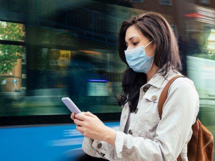 Portugal entra em estado de alerta: mulher com máscara a sair de autocarro