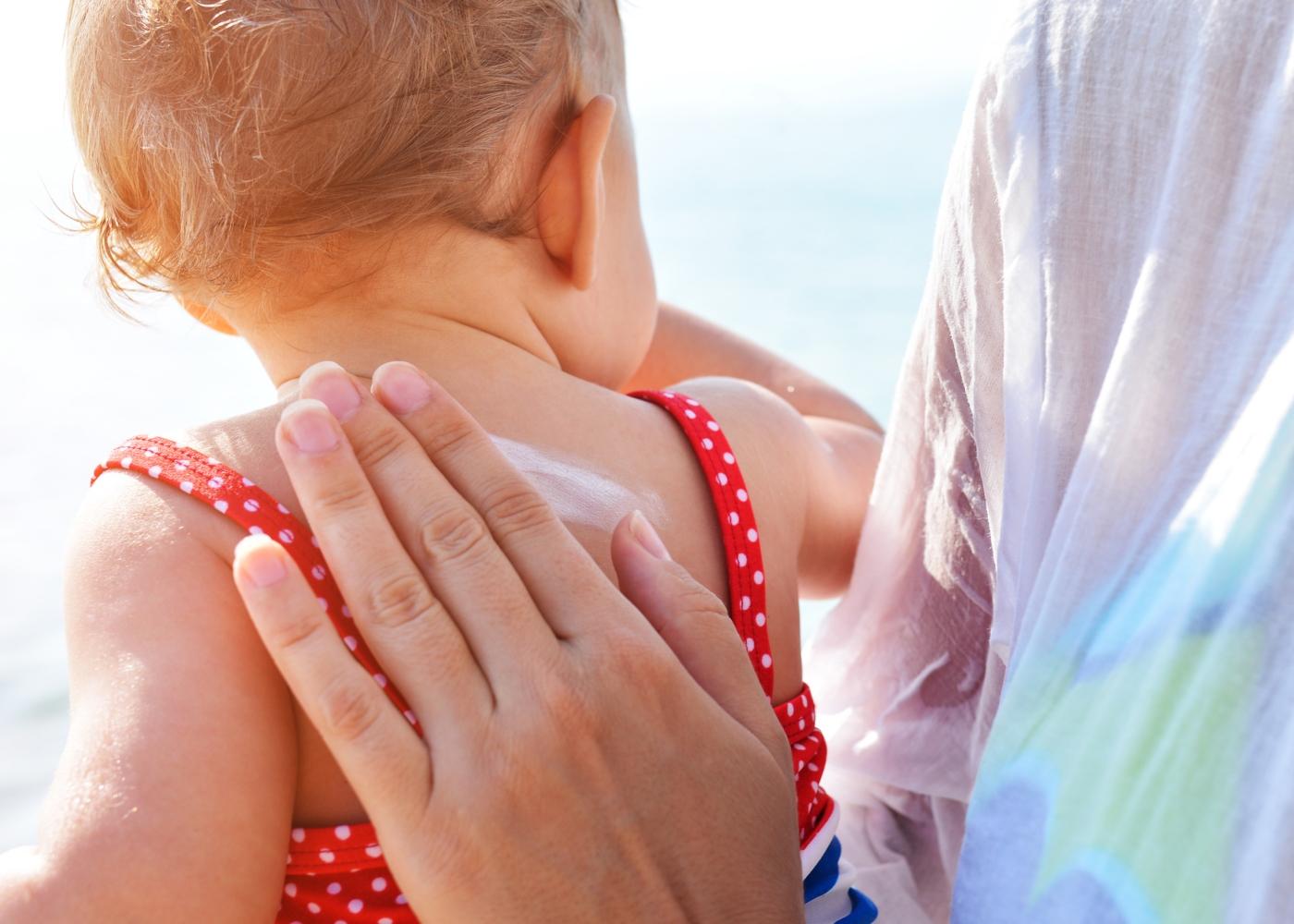 Mãe a aplicar protetor solar na filha bebé