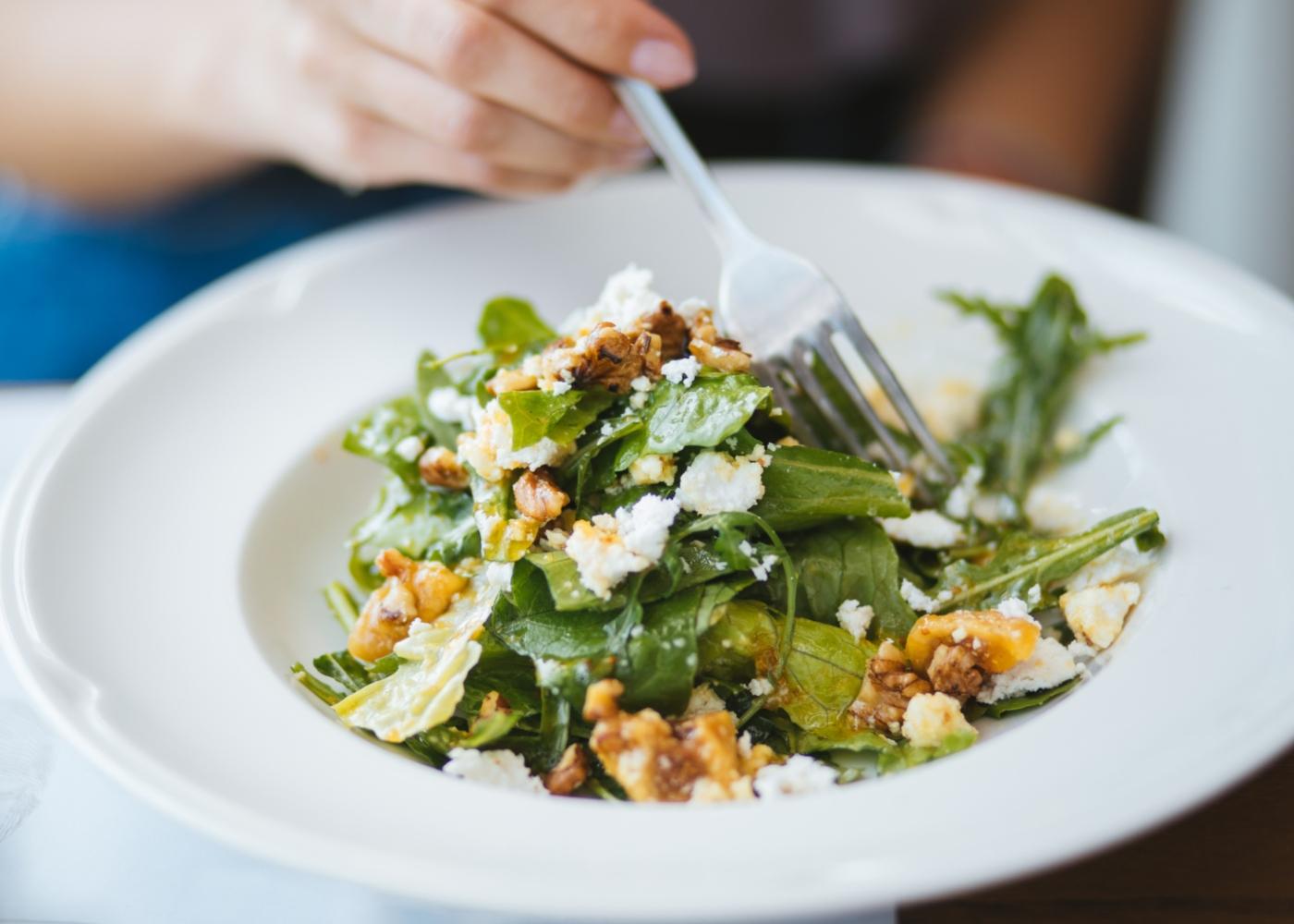 Mulher a comer salada com queijo fresco e nozes