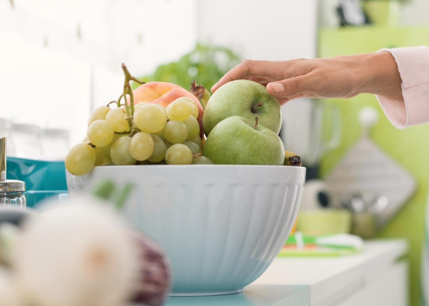 Mulher a tirar uma maça de uma taça com fruta