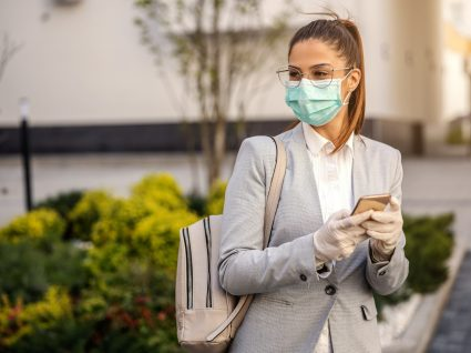 Uso de luvas: mulher com máscara e luvas a navegar no telemóvel