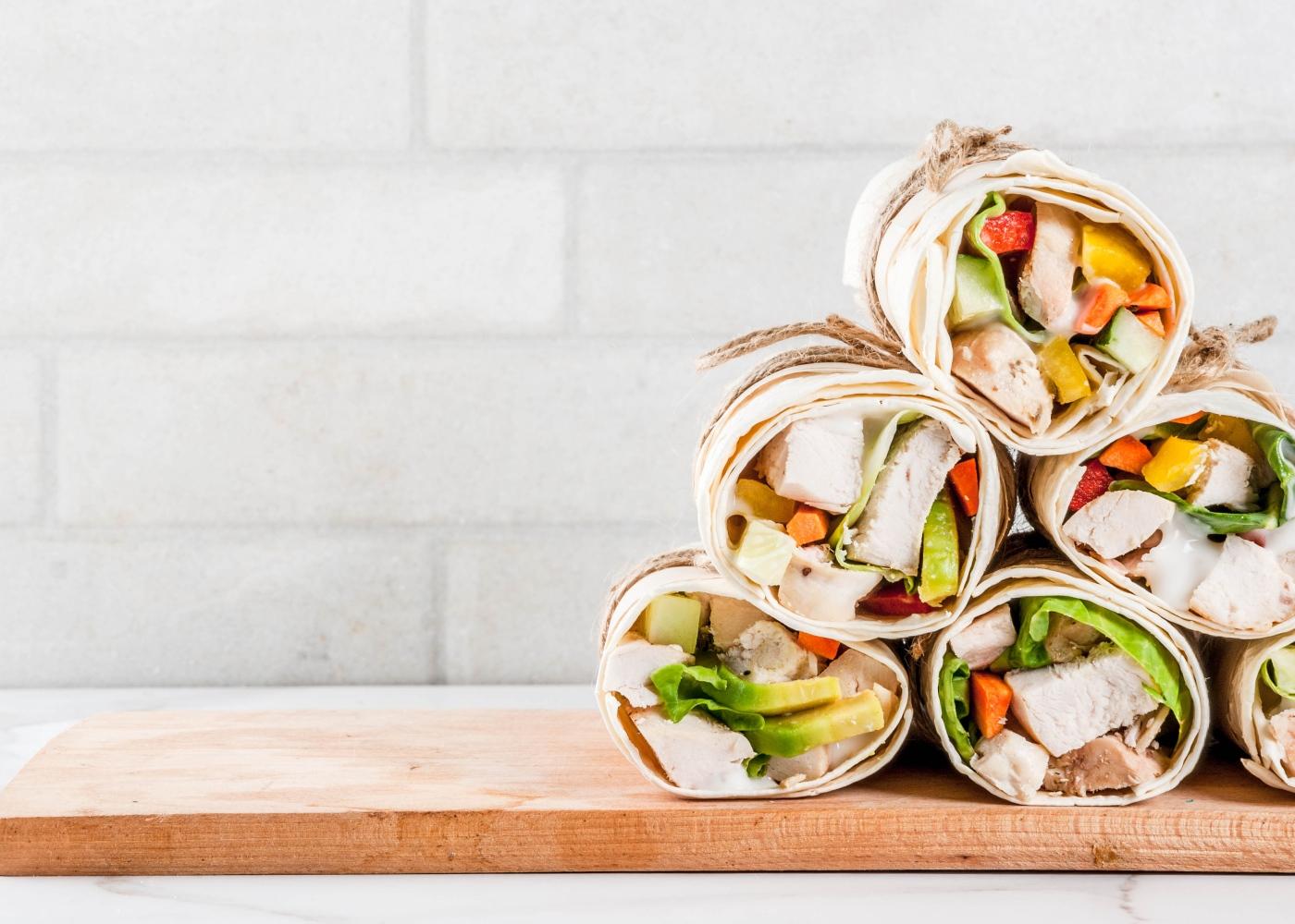 Wraps de frango e abacaxi em cima de tábua de madeira