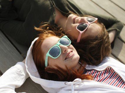 Adolescência: duas adolescentes com óculos de sol deitadas num pátio
