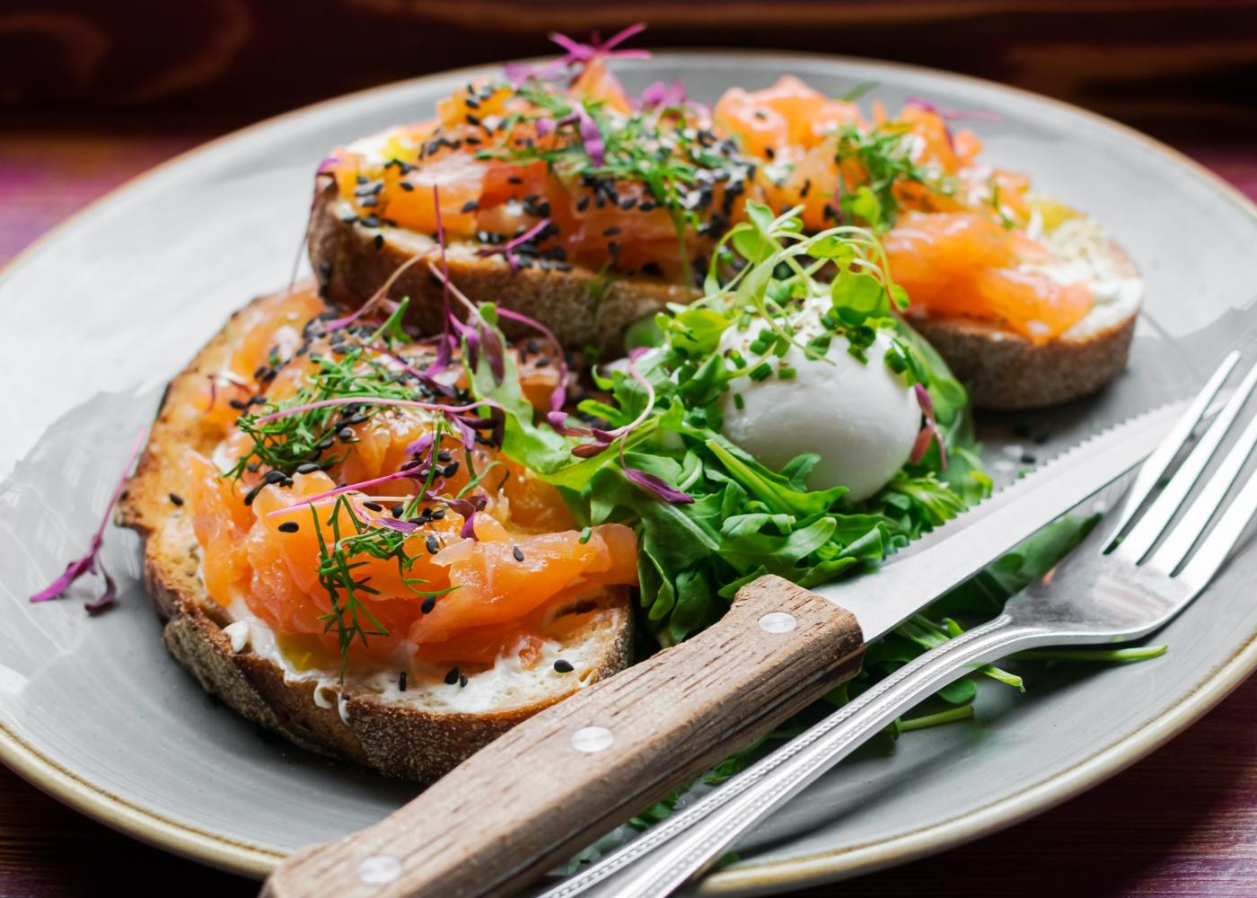 Prato com bruschettas de salmão fumado e ovo cozido