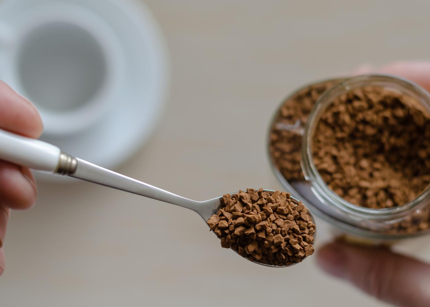Mulher a preparar chávena de café solúvel
