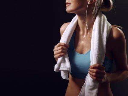 Cardio ou musculação: mulher a sua após treino no ginásio