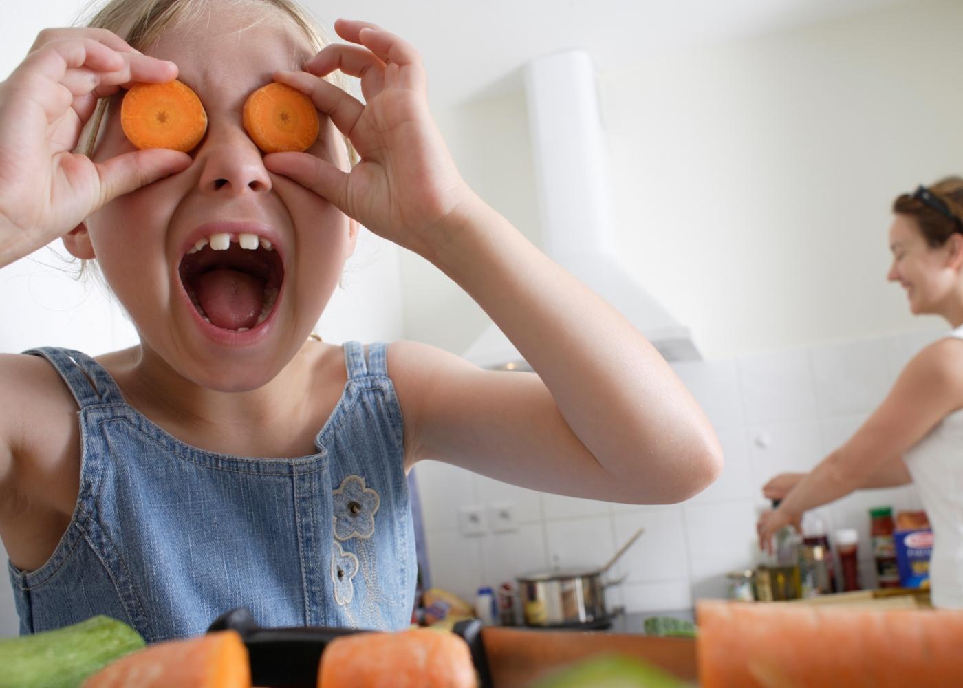 Criança a brincar com legumes