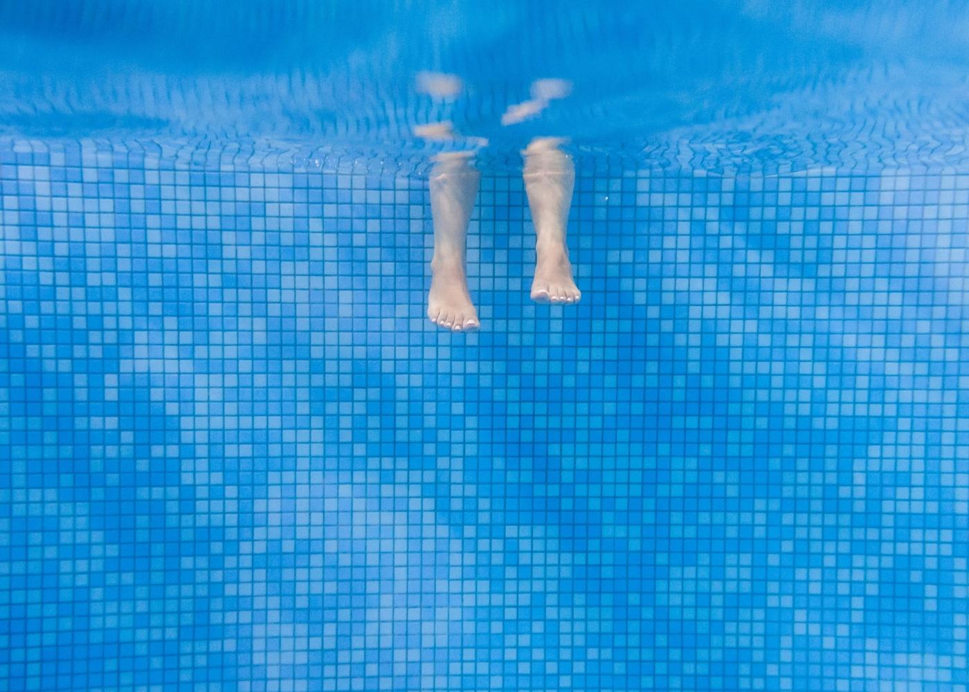 Crianças com os pés na piscina