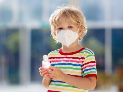 Crianças e máscaras: menino com máscara e álcool-gel na mão