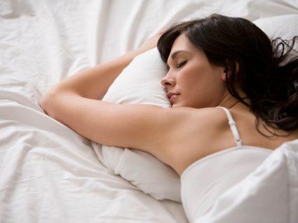 Dormir bem à noite: mulher deitada na cama a dormir