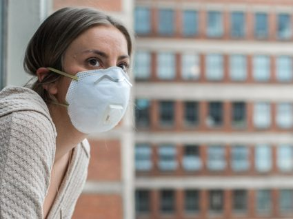 Grupos de risco para a COVID-19: mulher na janela de um hospital