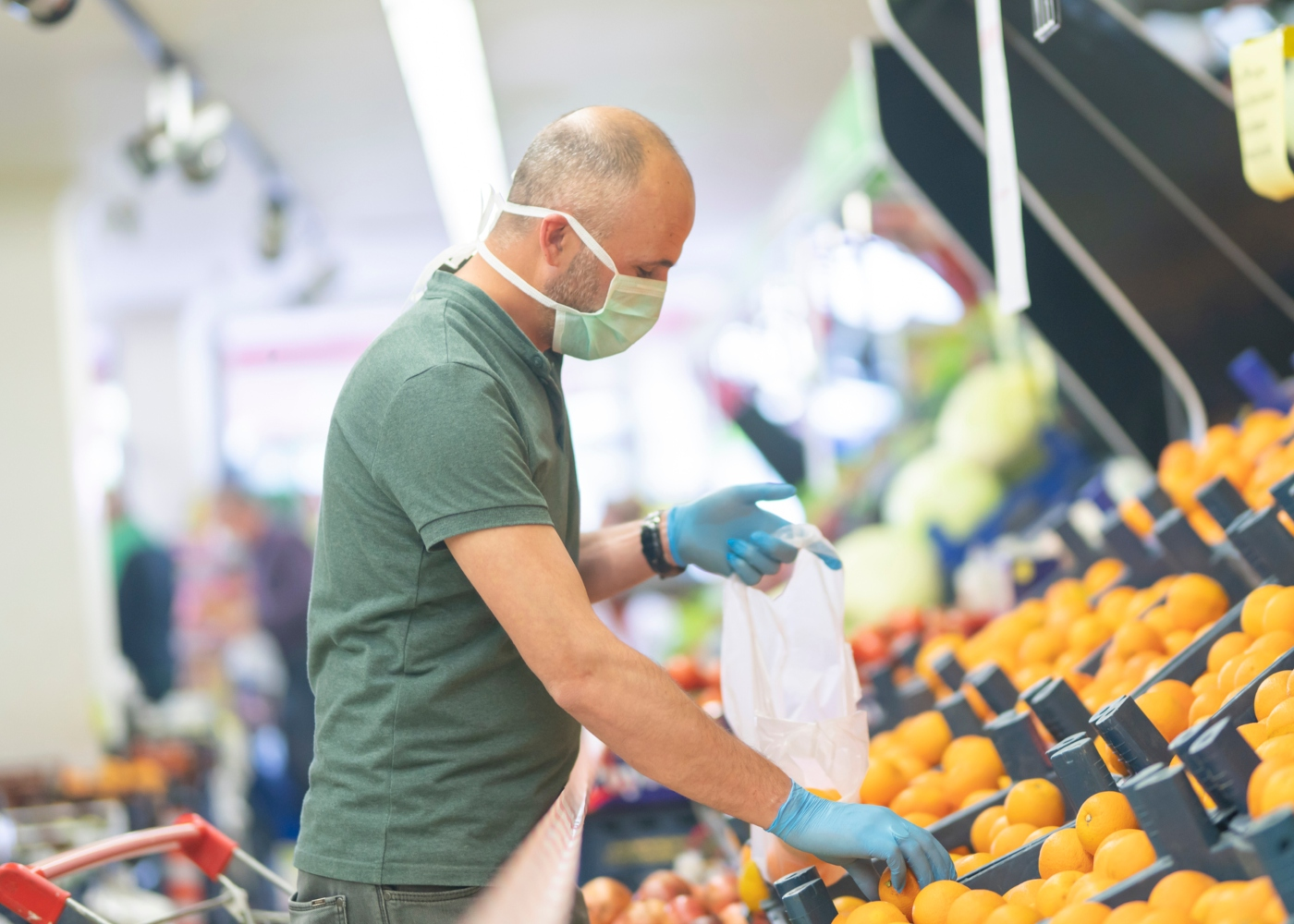 Homem com luvas e máscara no supermercado