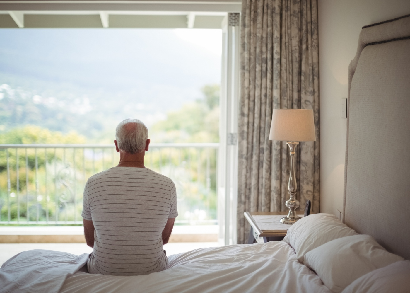 Homem pensativo sentado na cama
