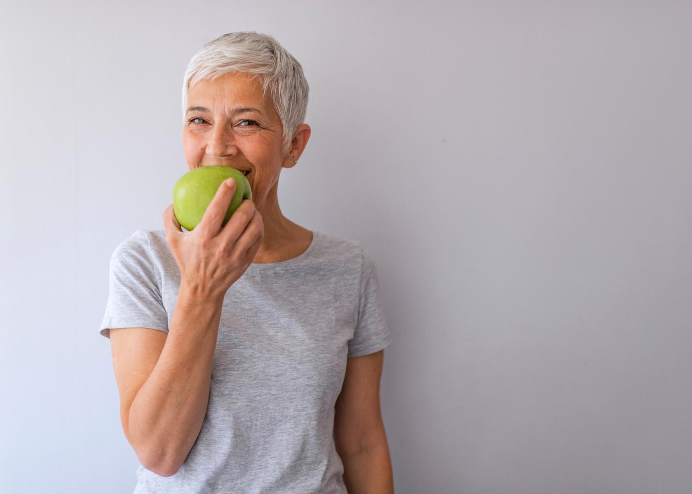 Idosa a comer uma peça de fruta