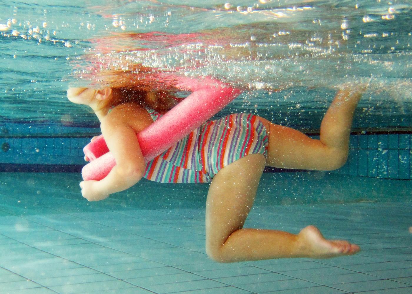 Menina com bóia na piscina