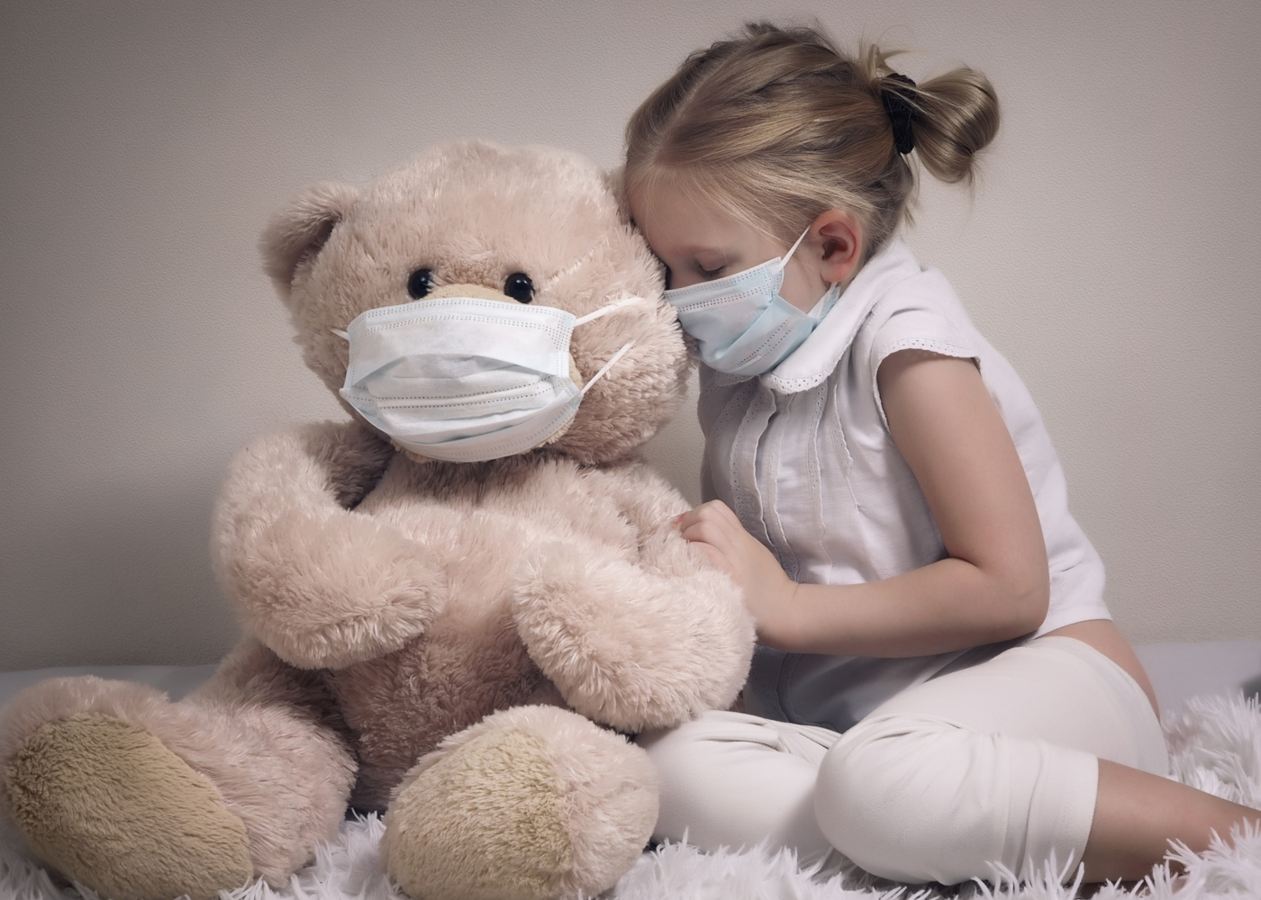 Menina e urso peluche com máscara