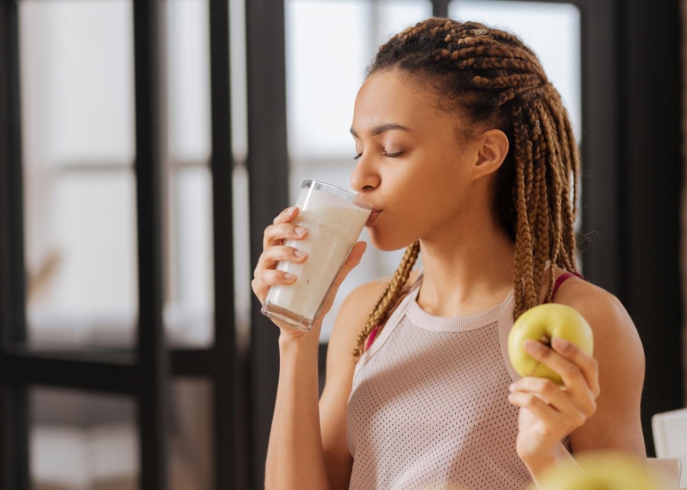 Mulher a beber batido e a comer uma maçã