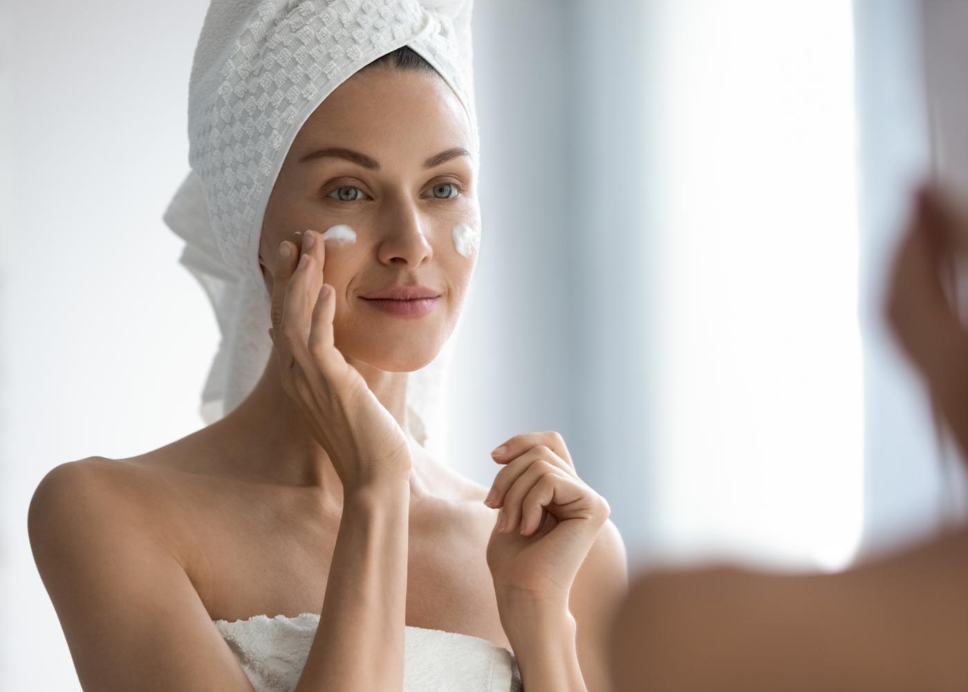 Mulher a aplicar creme hidratante na cara