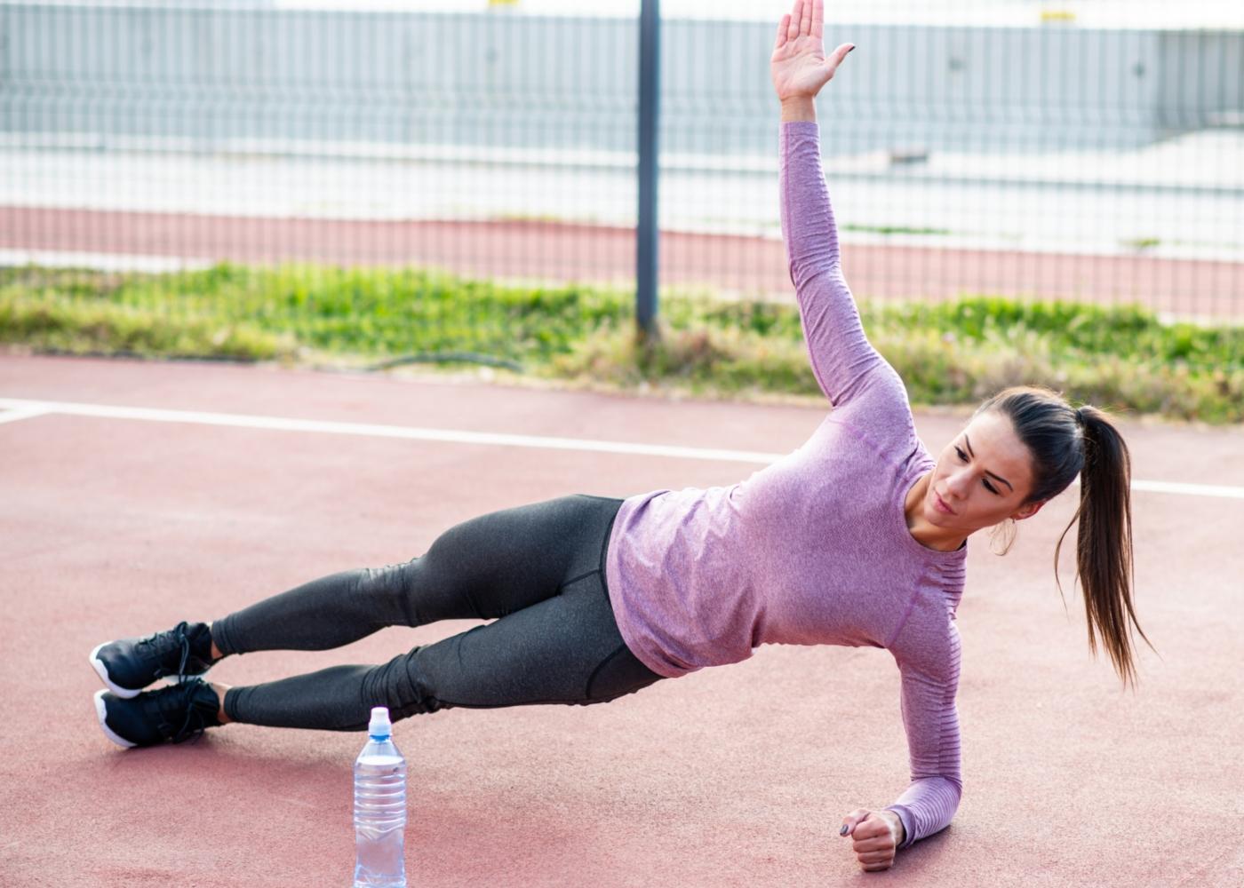 Mulher a fazer exercícios de prancha ao ar livre