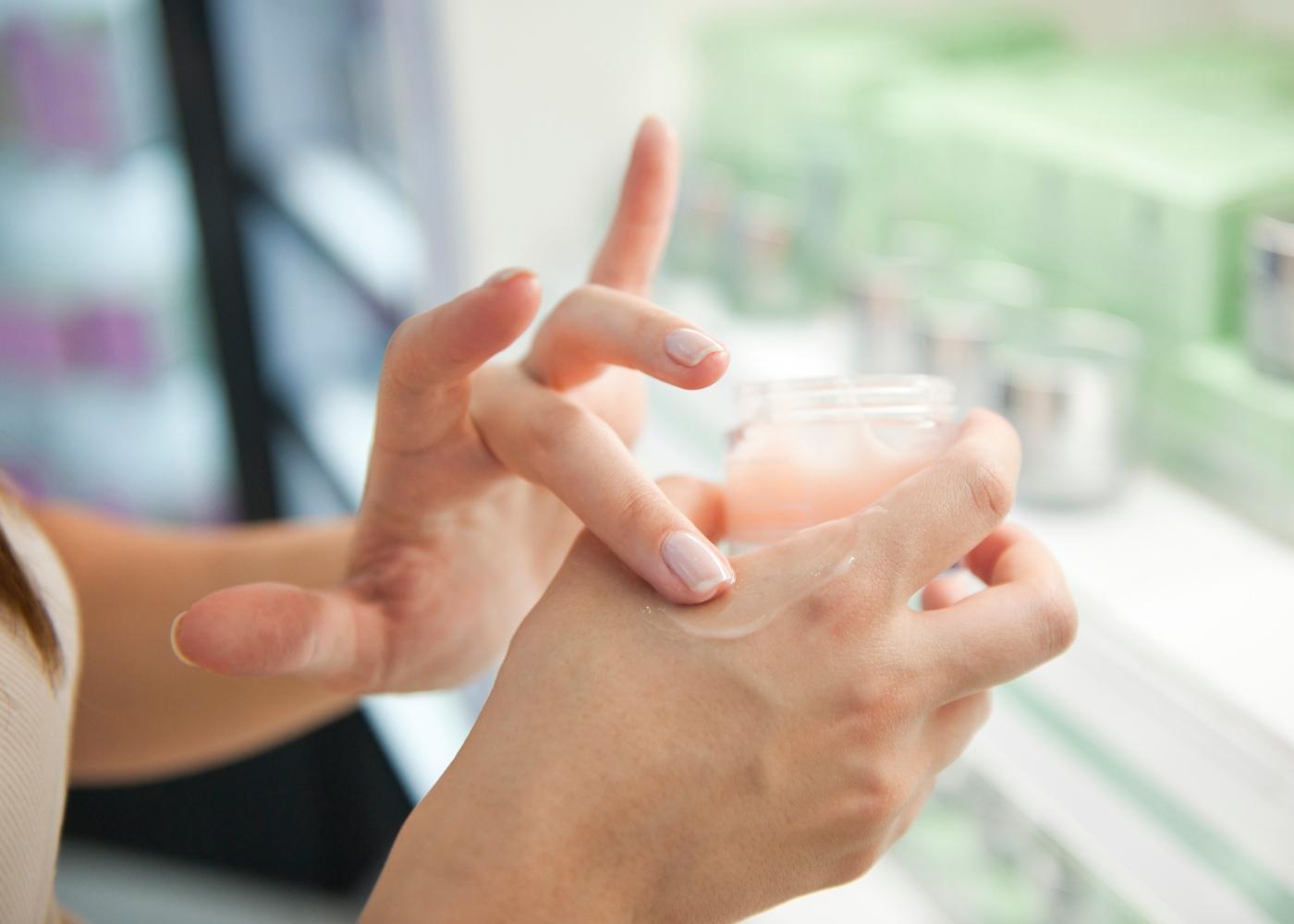 Mulher a hidratar mãos com vaselina