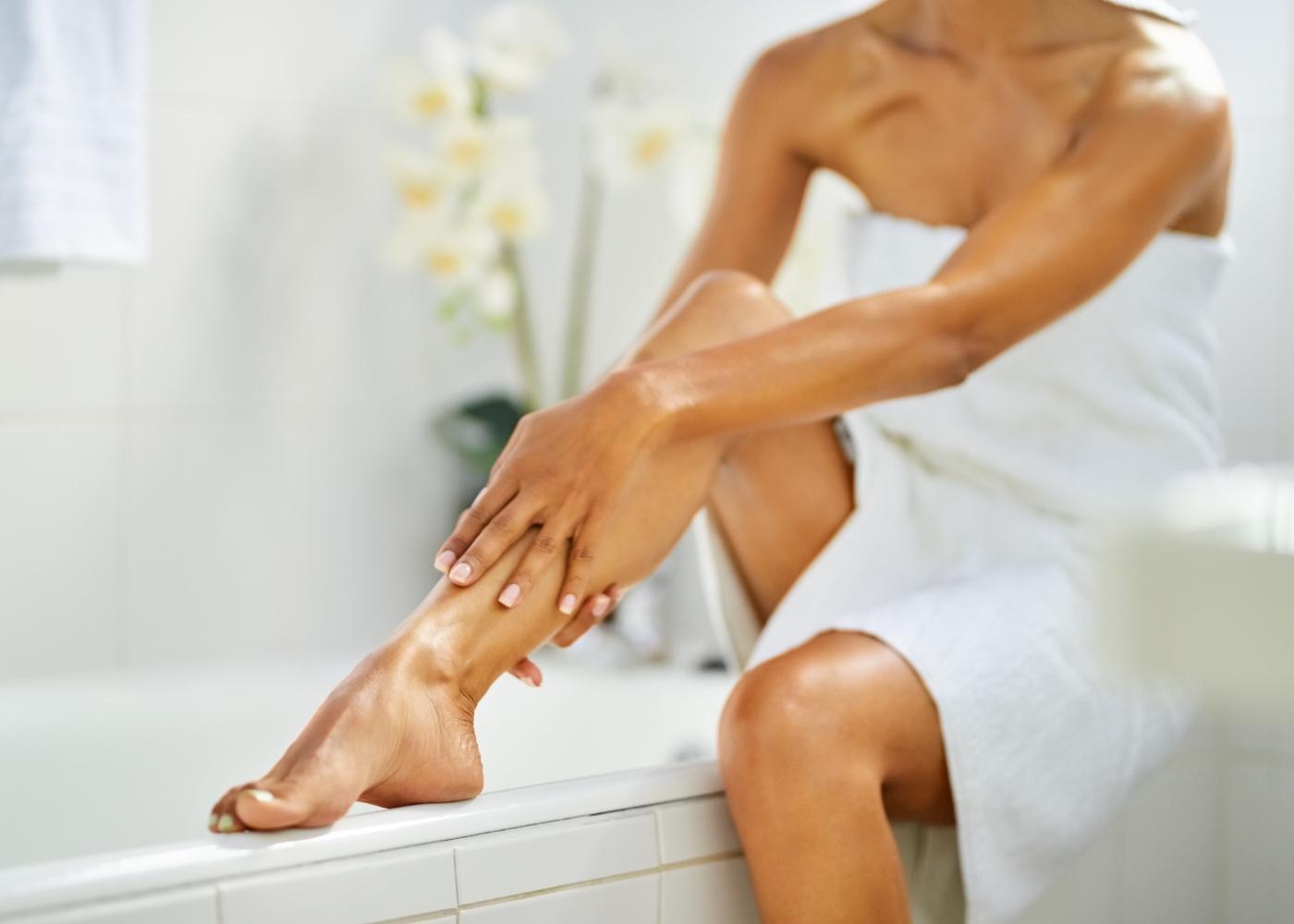 Mulher a hidratar a pele após o banho