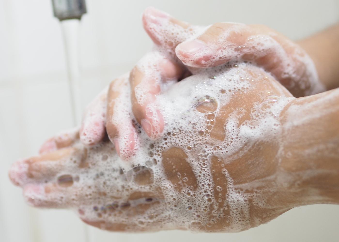 Mulher a lavar as mãos com sabão