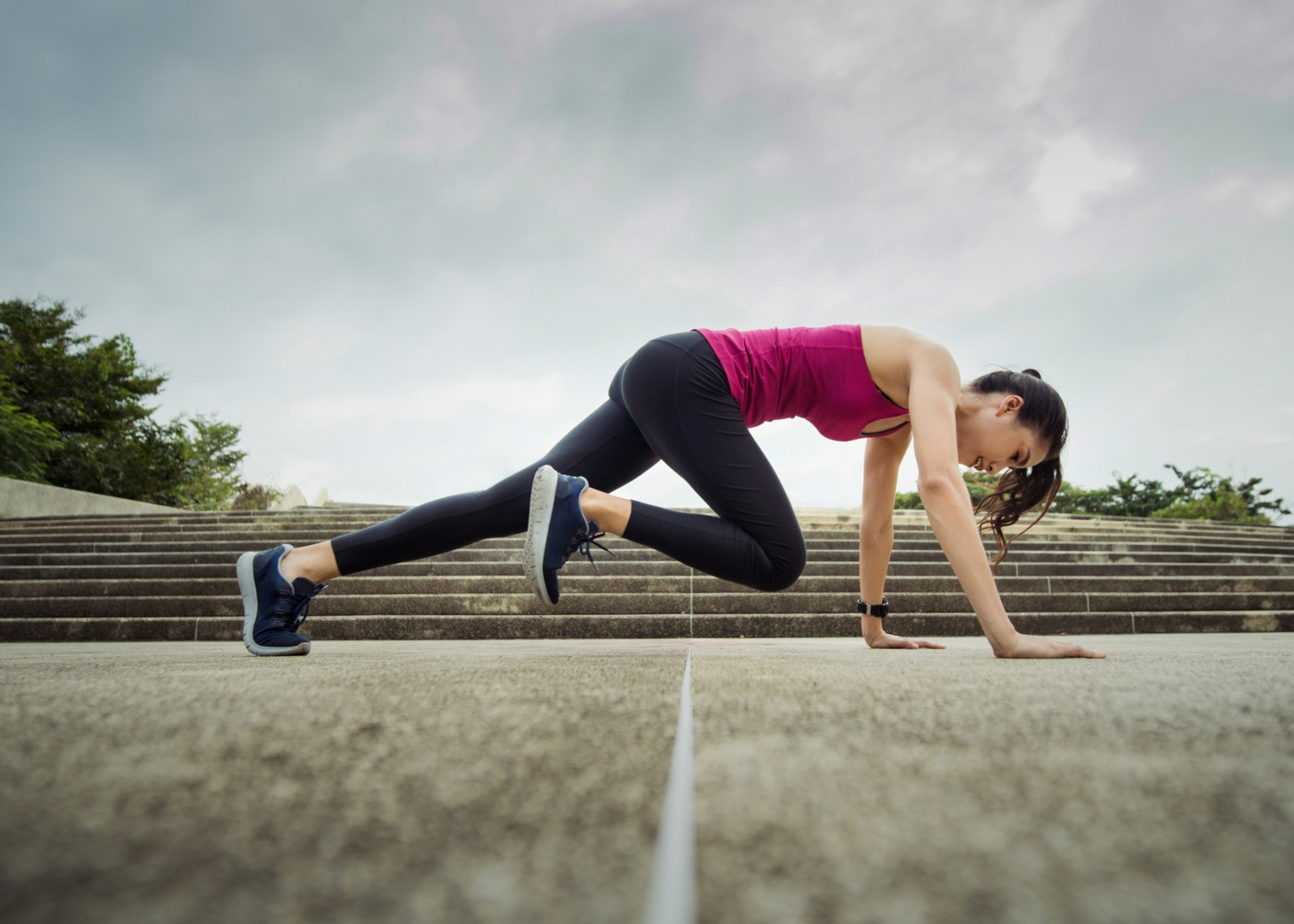 Mulher a fazer moutain climbers ao ar livre