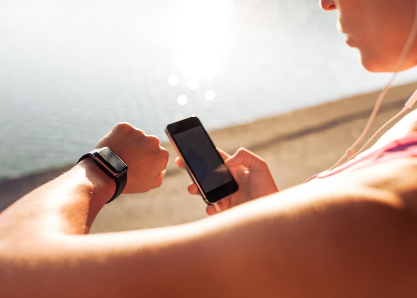 Mulher a sincronizar dispositivos para treinar ao ar livre