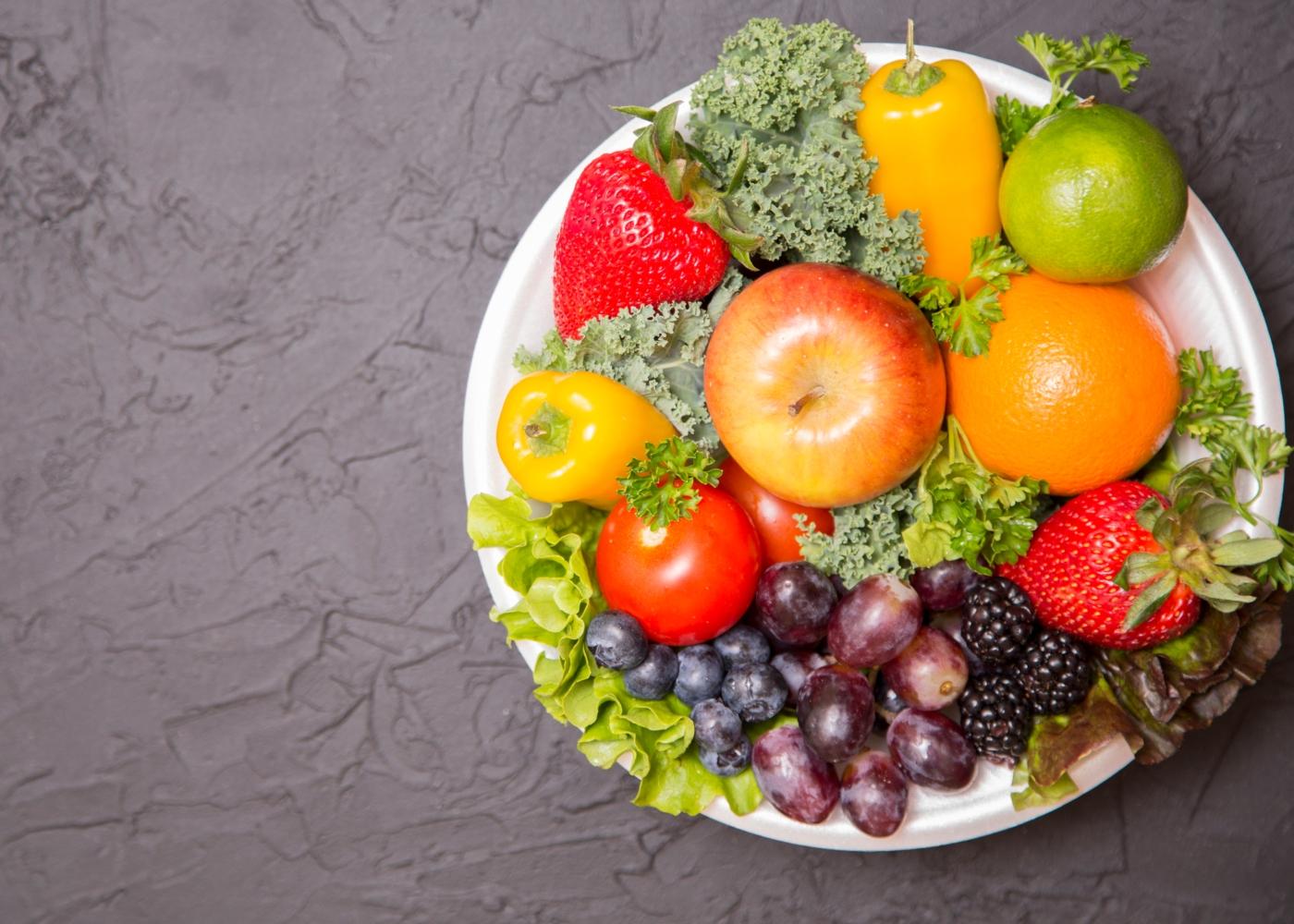 Prato com frutas e legumes em cima de mesa