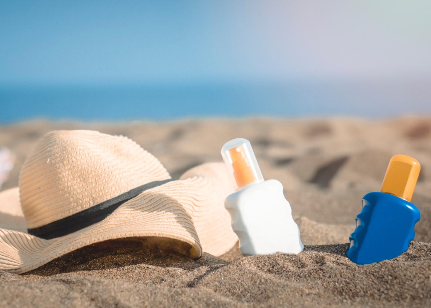 Protetor solar e chapéu na areia