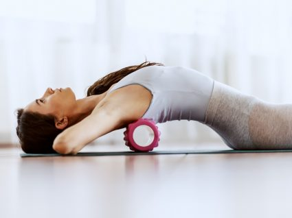Mulher a utilizar rolo de massagem após treino