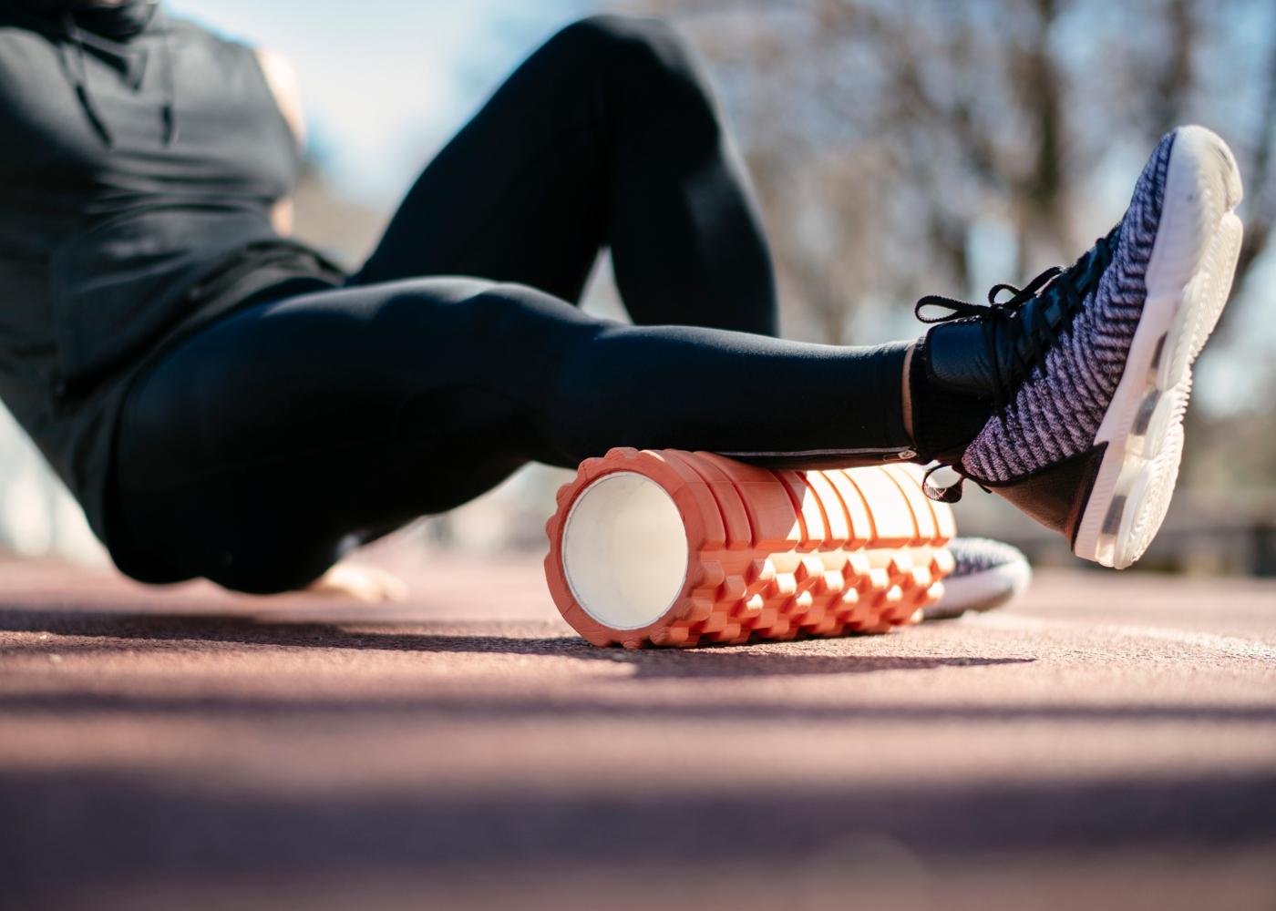 Homem a utilizar rolo de massagem nas pernas antes do treino ao ar livre