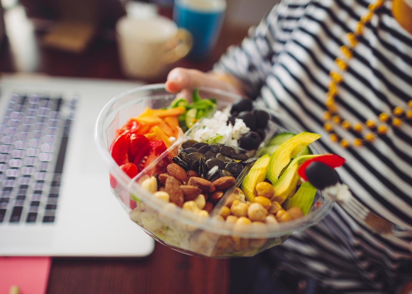 Mulher a segurar taça cheia de snacks saudáveis para o verão