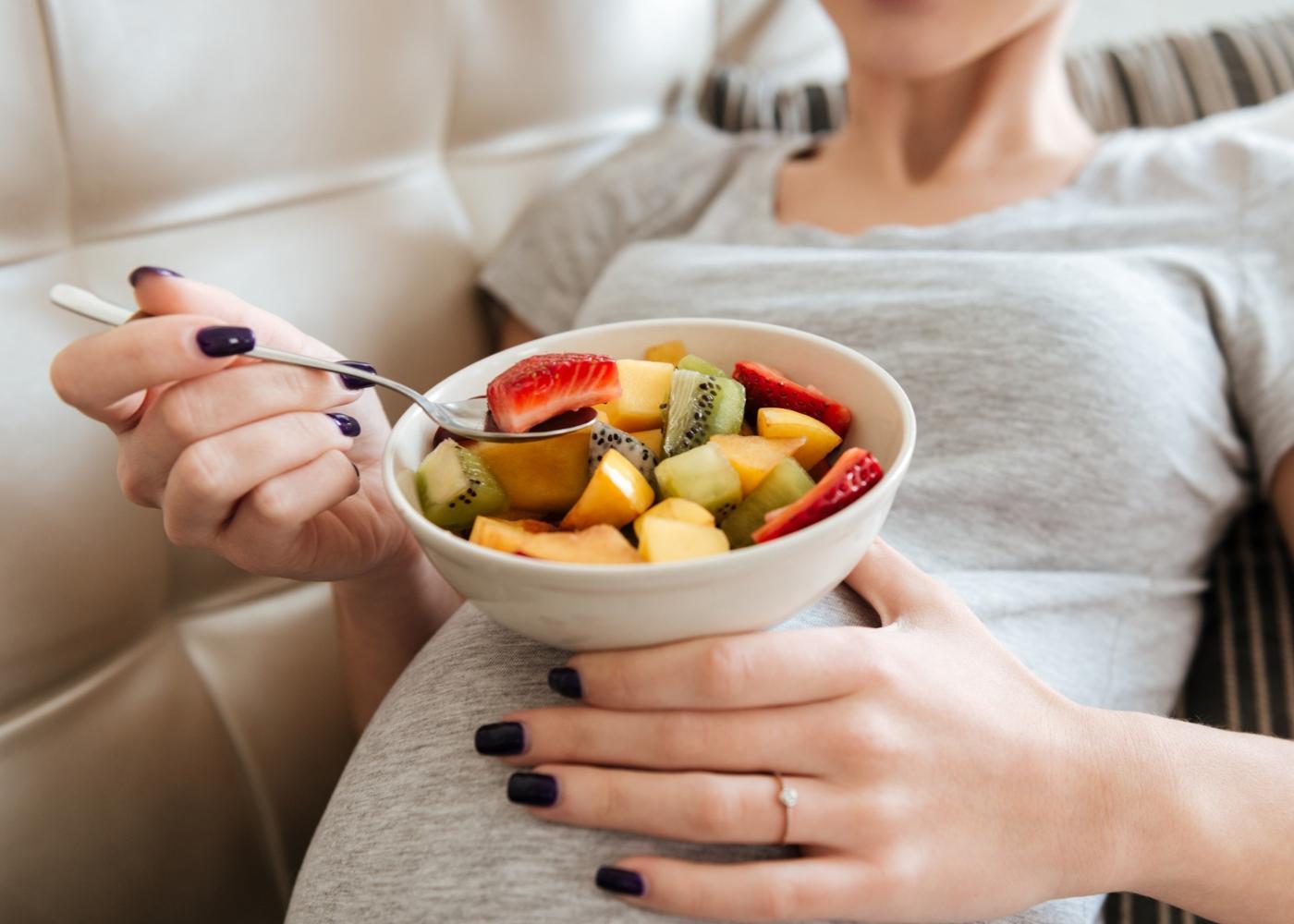 Mulher grávida a comer fruta
