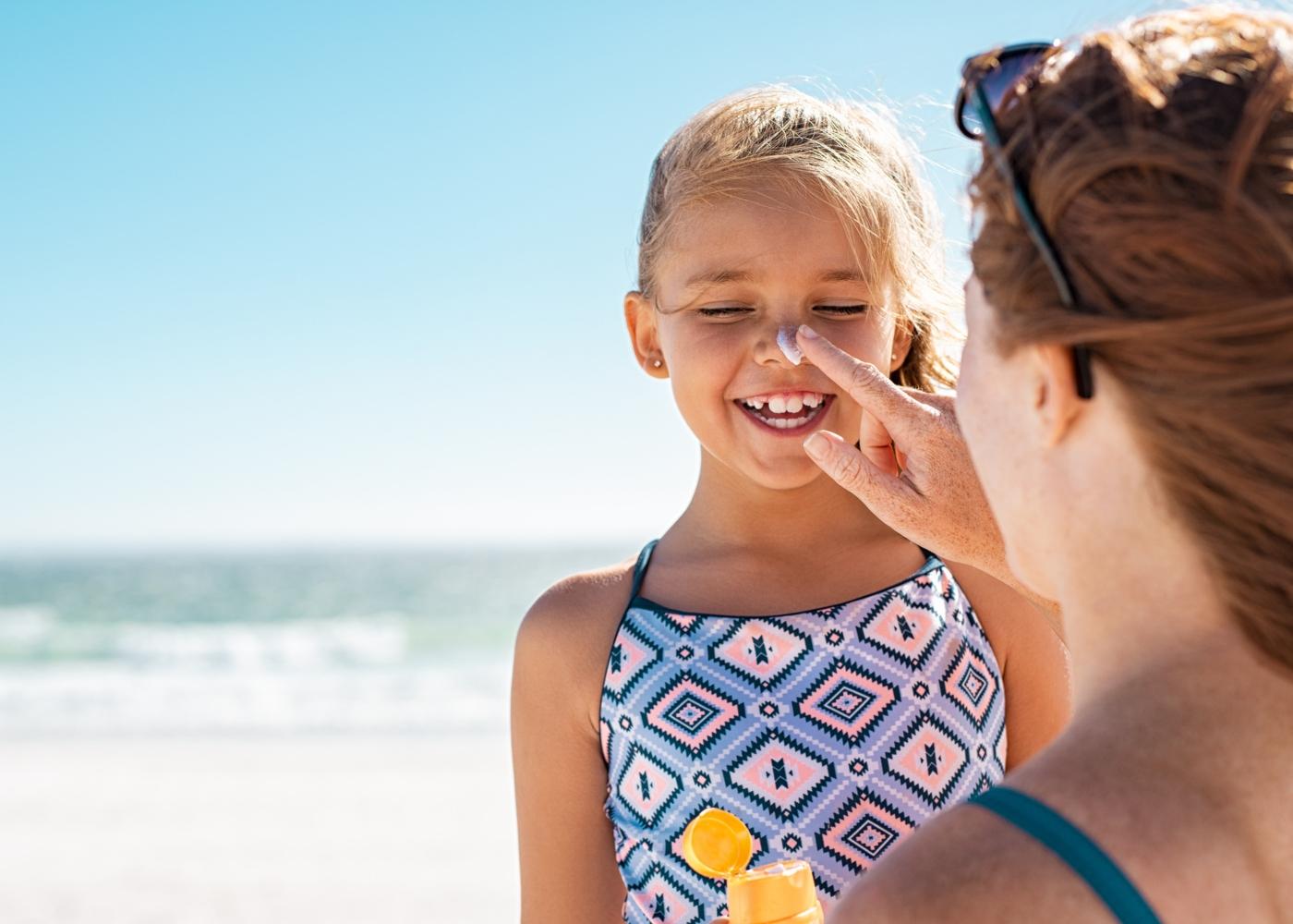 Mãe a aplicar protetor solar na cara da filha