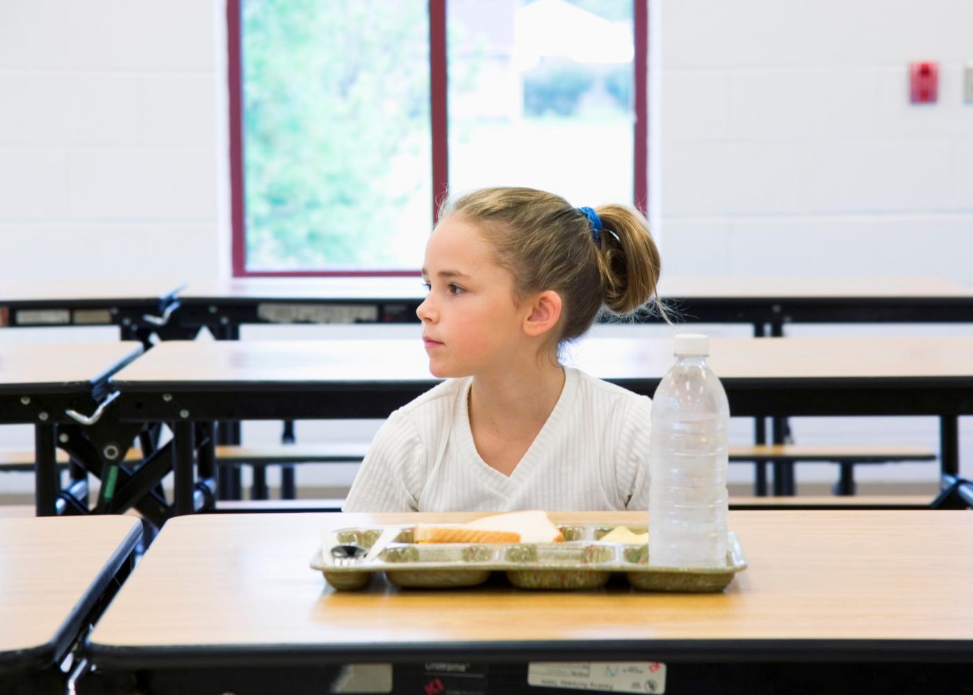 Menina a almoçar na cantina da Escola