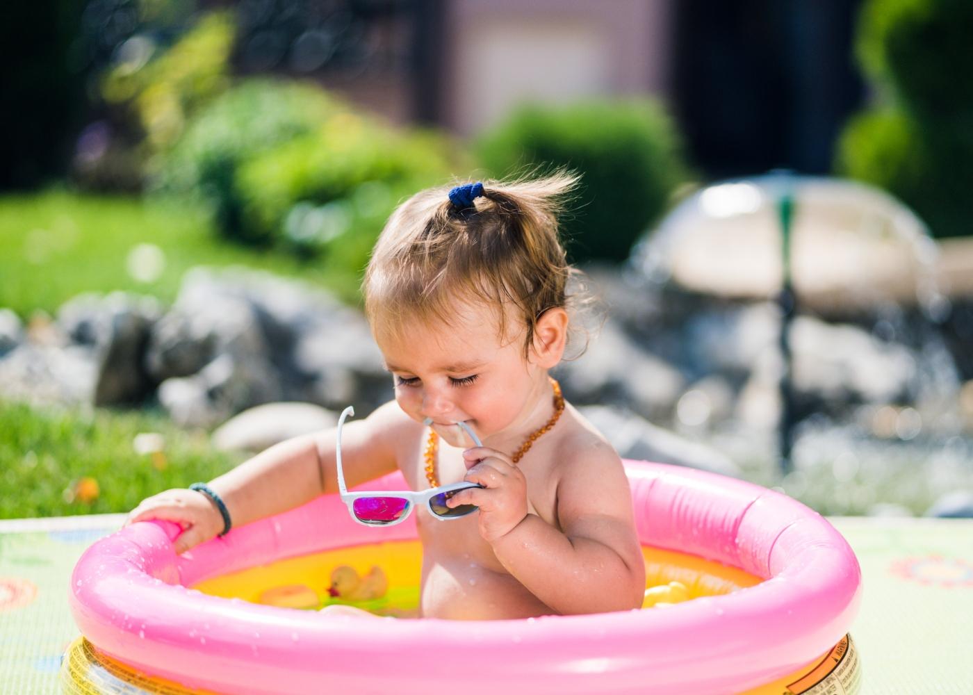 Menina com óculos de sol numa piscina insuflável