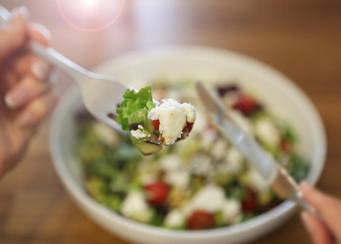 Mulher a comer uma salada ao almoço