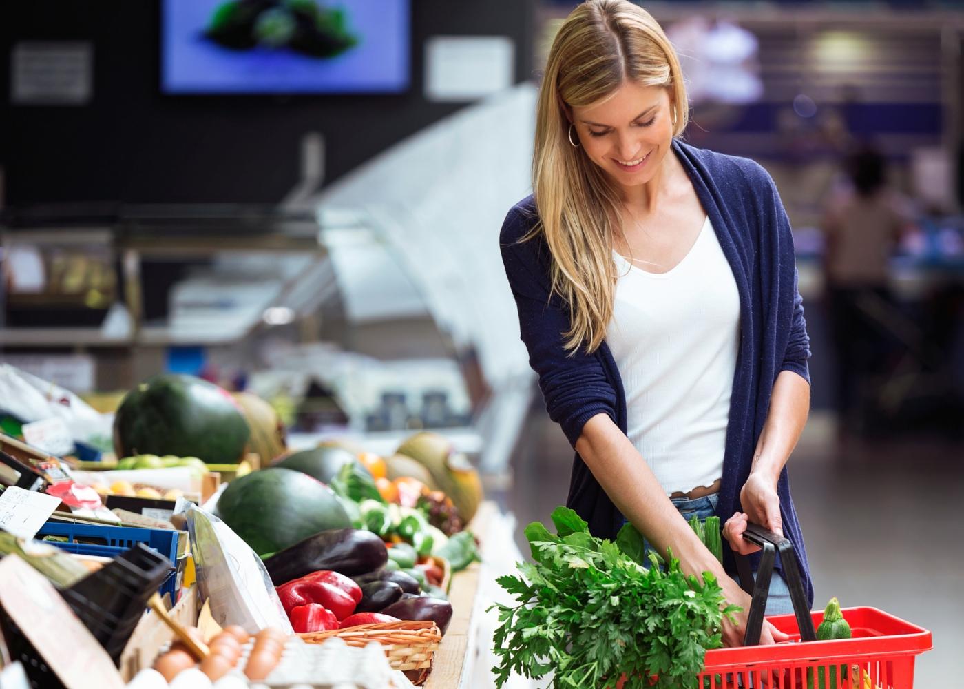 Mulher a comprar fruta e legumes no supermercado