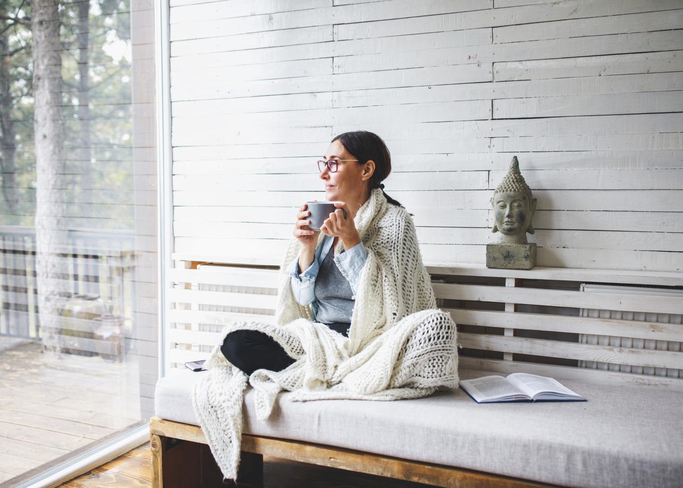 mulher no sofá com manta a beber chá