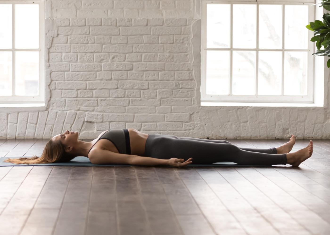 mulher deitada no tapete a praticar exercícios de respiração