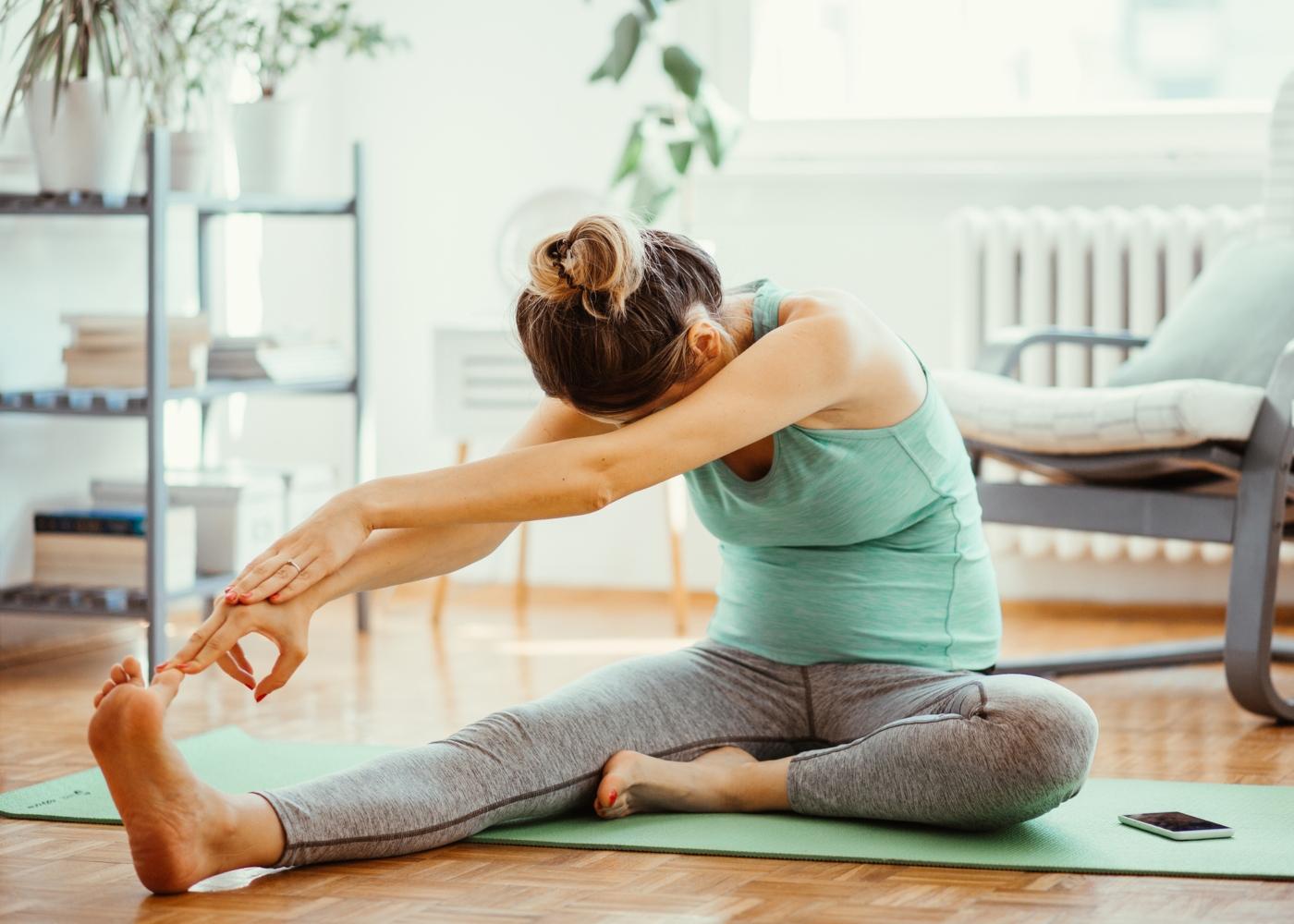 Mulher grávida a fazer exercício em casa