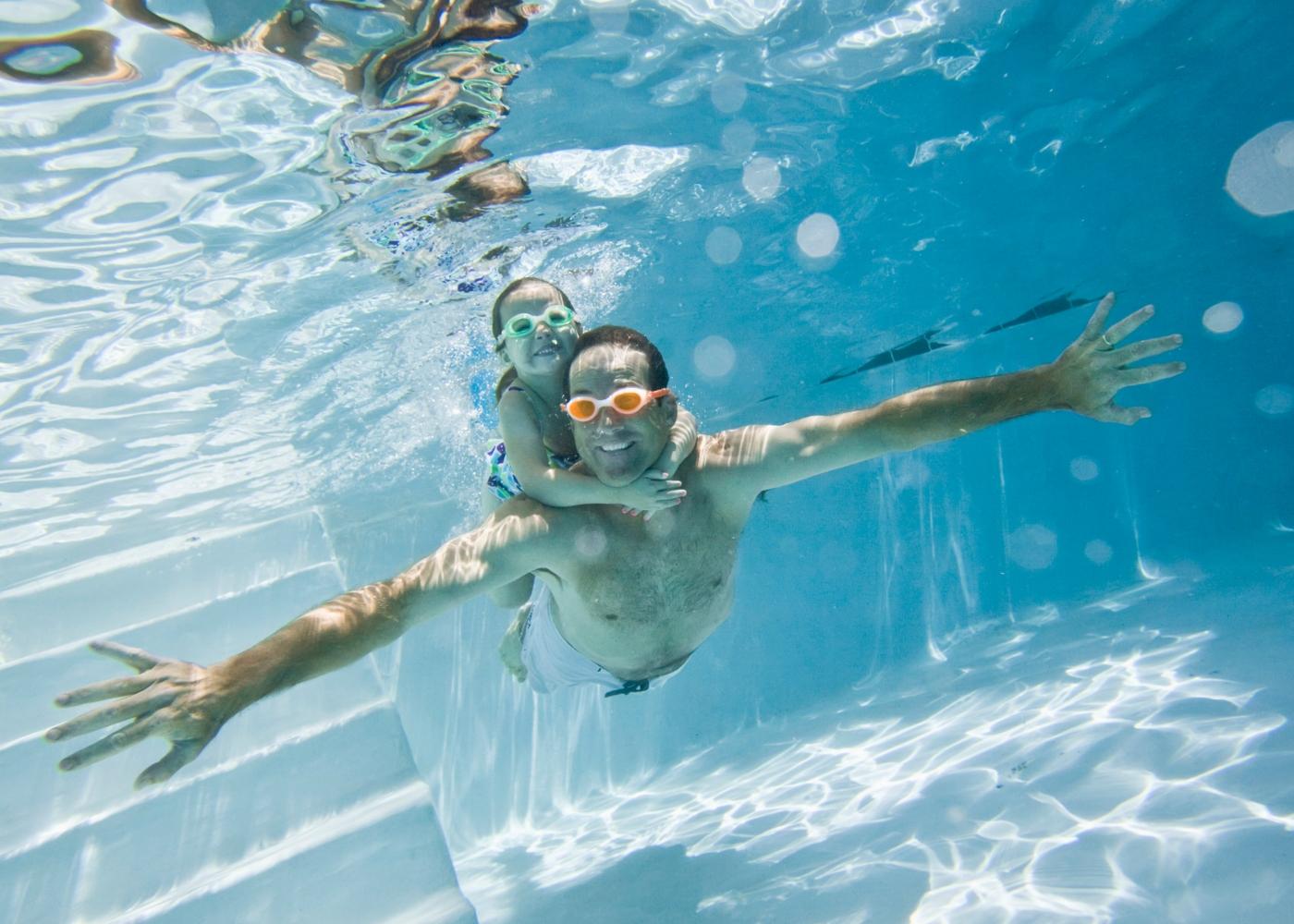 Pai e filha na piscina com óculos de natação