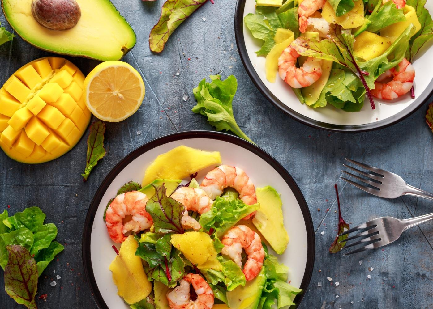 dois pratos de salada com camarão e manga